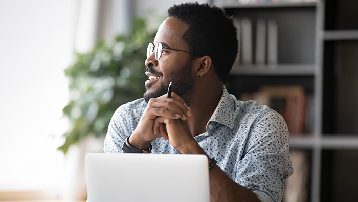Client trader smiling while looking away from laptop